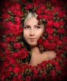 花框架的美女  有红色牡丹玫瑰的少女 库存图片