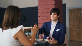 花梢衣服的英俊的年轻人提出提案给他心爱的年轻女人在浪漫日期期间在好的餐馆 影视素材