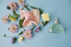 花的布置 花,芬芳,在蓝色背景的香水 库存照片