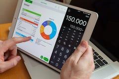 莫斯科/俄罗斯- 2013年3月2日:在一白色iPad的手上赞成在MacBook背景  计数预算 库存图片