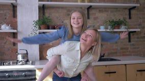 获得与妈妈的乐趣,快乐的女孩使用与母亲坐后面并且做在厨房里延伸的飞机胳膊