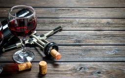 背景玻璃红葡萄酒 与拔塞螺旋的红酒 图库摄影