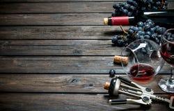 背景玻璃红葡萄酒 与拔塞螺旋的红酒 库存图片