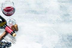 背景玻璃红葡萄酒 与的红酒葡萄和拔塞螺旋 免版税库存图片