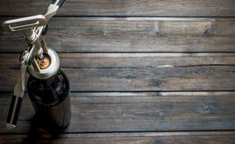 背景玻璃红葡萄酒 一个瓶与拔塞螺旋的白酒 免版税库存图片