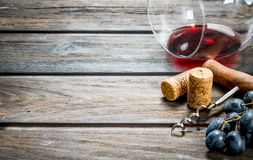背景玻璃红葡萄酒 一杯与拔塞螺旋和藤的红酒 图库摄影