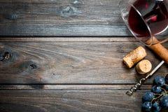 背景玻璃红葡萄酒 一杯与拔塞螺旋和藤的红酒 免版税库存图片