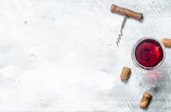 背景玻璃红葡萄酒 一杯红酒和拔塞螺旋 免版税库存照片