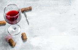 背景玻璃红葡萄酒 一杯红酒和拔塞螺旋 免版税图库摄影