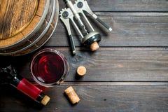 背景玻璃红葡萄酒 桶与拔塞螺旋的红酒 免版税图库摄影