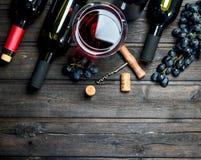 背景玻璃红葡萄酒 红酒用葡萄和拔塞螺旋 库存照片