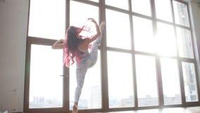 舒展和灵活性的概念 做舒展在白色内部的窗口附近的运动服的年轻女人 影视素材