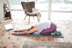 舒展所有身体肌肉的紫罗兰色绑腿的勤勉妇女 库存照片
