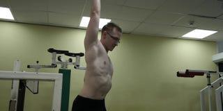 舒展胳膊的人在健身房锻炼前 站立室内做准备的健身坚强的男性运动员 股票录像
