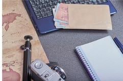 葡萄酒在膝上型计算机旁边的照片照相机和与金钱的一个信封在欧元 免版税库存照片