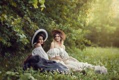 葡萄酒衣裳和帽子的两个女孩 免版税库存图片
