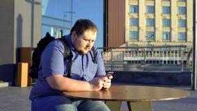 肥胖年轻人卷动智能手机,在室外咖啡馆的开会,懒惰生活方式 库存图片