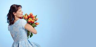 蓝色礼服的可爱的妇女有红色和黄色郁金香花束的  库存照片