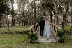 蓝色礼服的美丽的女傧相妇女和花束与她的在一个正式婚礼庆祝事件的日期外面在木头 库存照片