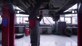 自动服务,专业技术员男性运作在推力的汽车在修理期间和检查下在车间 股票录像