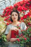 自杜娟花温室读书和作梦在一件美丽的减速火箭的礼服的美丽的成人女孩 免版税库存照片