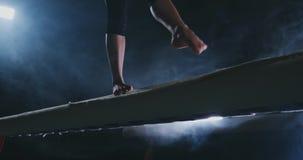 腿专业女孩体操运动员在抽烟的慢动作跳在平衡木 妇女的艺术性的体操 股票视频