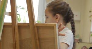 艺术家的年轻手,小妇女艺术家绘与刷子的一块帆布,桌和凹道坐帆布 过程  股票录像