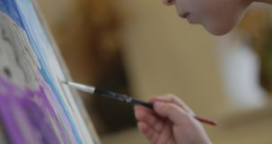 艺术家的年轻手,小妇女艺术家绘与刷子的一块帆布,桌和凹道坐帆布 过程  股票视频