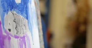 艺术家的年轻手,小妇女艺术家绘与刷子的一块帆布,表和凹道坐帆布 过程  影视素材
