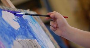 艺术家的年轻手,小妇女艺术家绘与刷子的一块帆布,表和凹道坐帆布 过程  股票录像