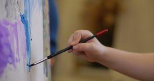 艺术家的年轻手,小妇女艺术家绘与刷子的一块帆布,表和凹道坐帆布 过程  股票视频
