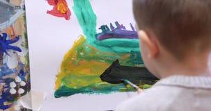 艺术家的年轻手,小孩艺术家绘与刷子的一块帆布,桌和凹道坐帆布 过程  股票视频