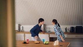 英俊的亚裔人在家跳舞与他获得乐趣和亲吻在厨房的逗人喜爱的女朋友穿轻松的衣物 股票录像