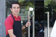 英俊的亚裔男性咖啡馆或餐馆侍者所有者受欢迎的客人在他的企业地方通过打开玻璃门 库存图片