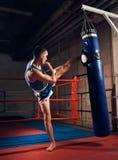 英俊的反撞力拳击手训练踢的和猛击的把装箱的袋子 库存图片