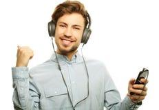 英俊的年轻人佩带的耳机和听到音乐 免版税库存照片