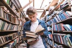 英俊的年轻人在有书的一个老公立图书馆里站立在他的手上并且读 图库摄影
