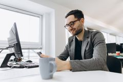 英俊的商人使用一个智能手机并且微笑着,当工作在办公室时 免版税库存图片