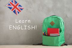 """英国的背包、旗子和笔记本对有文本的""""水泥墙壁;学会英语 免版税库存图片"""