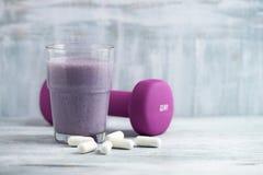 蛋白质震动玻璃用牛奶和蓝莓 BCAA氨基酸和紫罗兰色哑铃在背景中 体育营养 免版税库存图片