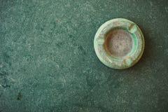 老多灰尘的绿色烟灰缸一个选材台 库存照片