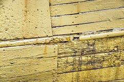 老被风化的黄色木船的船身 免版税库存照片