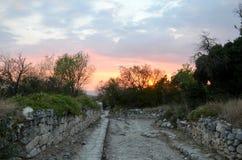 老被铺的路的废墟在夏天日落天空的背景的在桃红色、紫色和蓝色的 库存照片