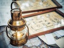 老黄铜色船灯笼在海的地图站立在与海结的图象的图片附近 免版税库存图片
