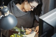 考虑文本和写在笔记本的可爱的妇女自由职业者作家 免版税库存照片