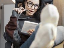 考虑文本和写在笔记本的可爱的妇女自由职业者作家 库存照片