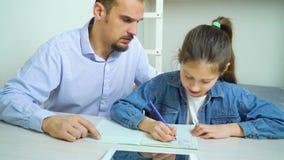 责骂他的女儿的恼怒的父亲,当她做着家庭作业时 影视素材