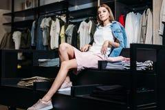购物 时髦的衣裳的Beautifu模型深色的fashionablel女孩,摆在服装店,衣裳一个新的趋向  钞票 免版税库存图片