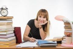 È impegnata alla tavola stipata di con i libri nella biblioteca con gli sguardi di un sorriso nel telaio Fotografia Stock Libera da Diritti