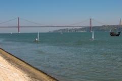 25ème April Bridge à Lisbonne et des bateaux à voile, Portugal Image stock